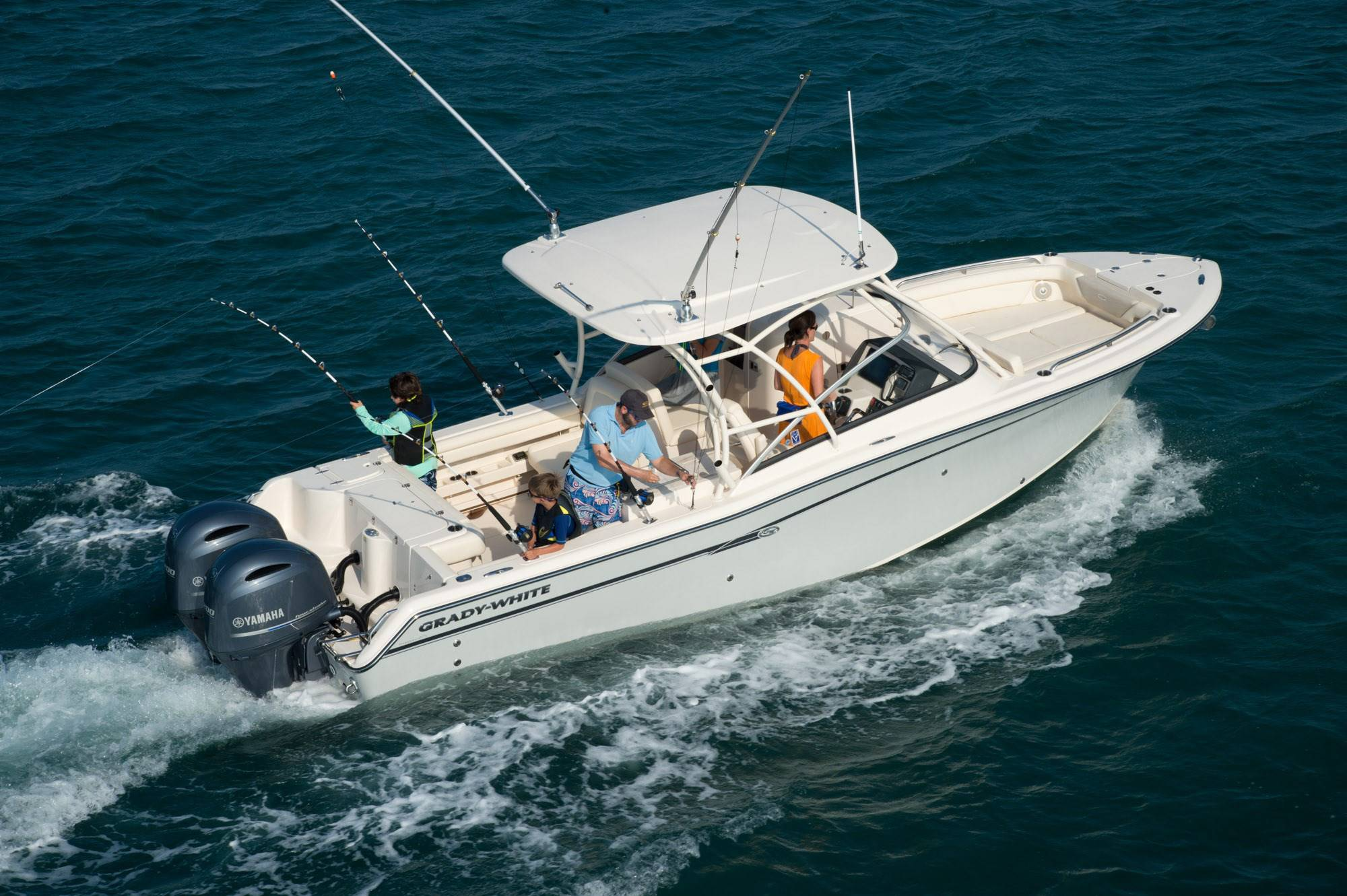 A family enjoys fishing on a Grady-White dual console boat.