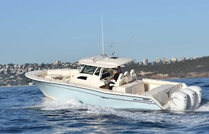 Grady-White Canyon 376 37-foot center console boat running port side city background