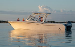 Grady-White Freedom 275 27-foot dual console boat port side with family at sunrise