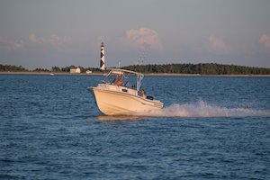 Grady-White Boats Adventure 208 20-foot Walkaround Cabin fishing boat running in front of lighthouse