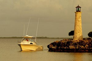 Grady-White Marlin 300 30-foot walkaround cabin boat cruising by lighthouse