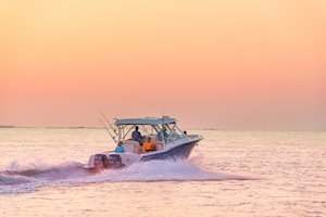 Grady-White Freedom 325 32-foot dual console fishing boat running at sunset